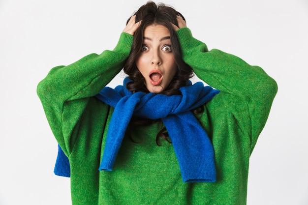 Hermosa mujer joven asustada confundida vestida con un suéter verde posando aislada en la pared blanca.