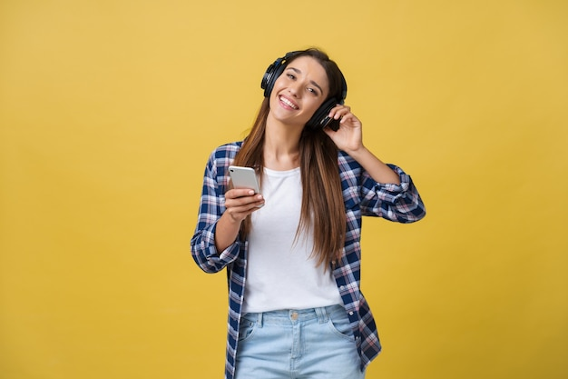 Hermosa mujer joven en auriculares escuchando música y bailando sobre fondo amarillo.