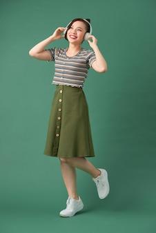 Hermosa mujer joven en auriculares escuchando música y bailando en verde