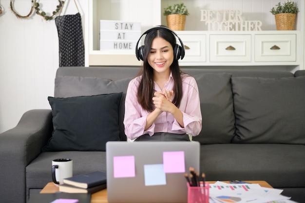Una hermosa mujer joven con auriculares está haciendo una llamada de videoconferencia a través de la computadora en casa, concepto de tecnología empresarial.