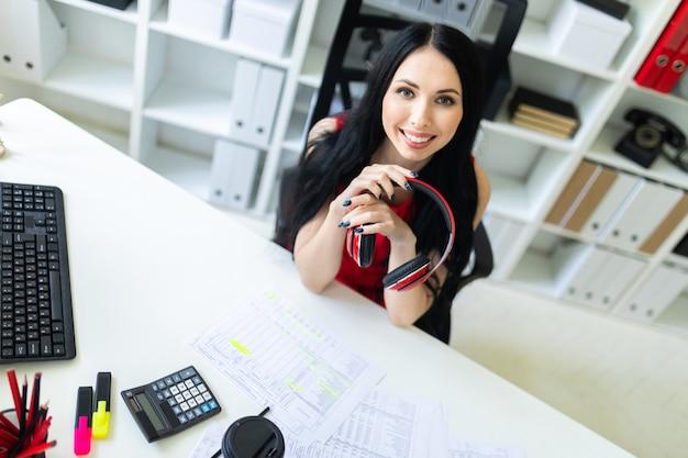 Hermosa mujer joven con auriculares en las manos está sentado en la oficina en la mesa.