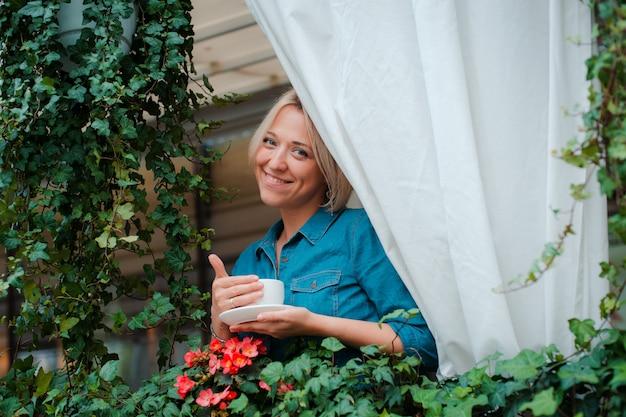 Hermosa mujer joven en el balcón con flores y cortina blanca disfrutando de una mañana taza de café.