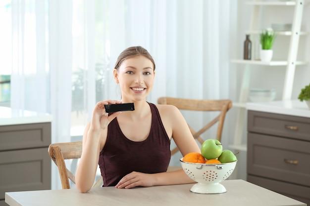 Hermosa mujer joven con barra de energía sentado en la mesa. concepto de dieta