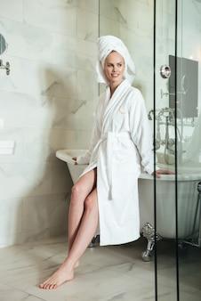 Hermosa mujer joven en bata de baño y toalla en la cabeza