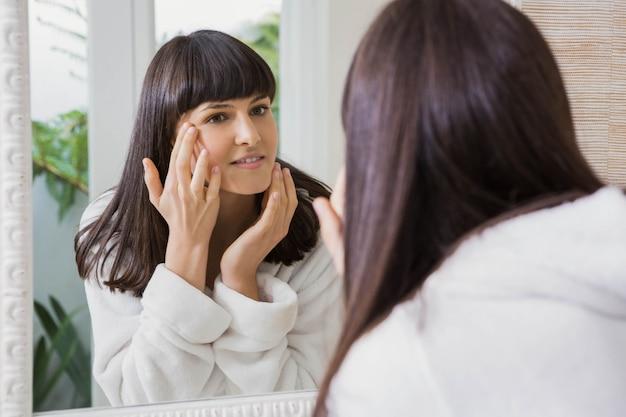 Hermosa mujer joven con bata blanca mirando en el espejo