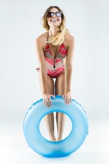 Hermosa mujer joven en bikini jugando con flotador. aislado en blanco.