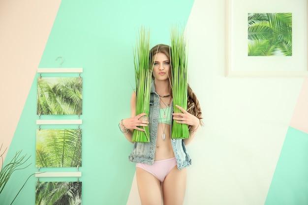 Hermosa mujer joven en bikini con plantas exóticas en casa