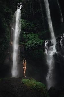 Hermosa mujer joven en bikini relajante frente a la cascada. chica de viaje de imagen de concepto de ecoturismo