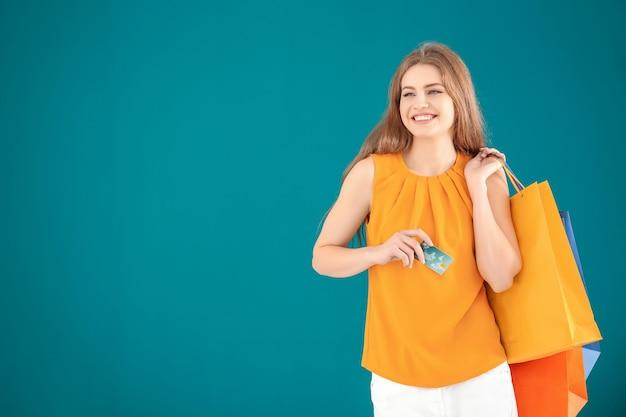 Hermosa mujer joven con bolsas de la compra y tarjeta de crédito en la superficie de color