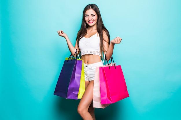 Hermosa mujer joven con bolsas de compras en la pared turquesa