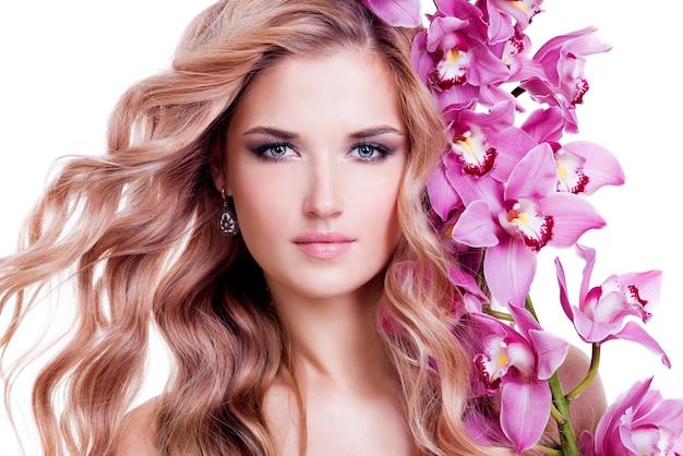 Hermosa mujer joven y bonita con piel sana y flores rosadas cerca de la cara - aislado en blanco.