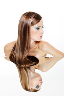 Hermosa mujer joven con cabello exuberante y su reflejo en el espejo