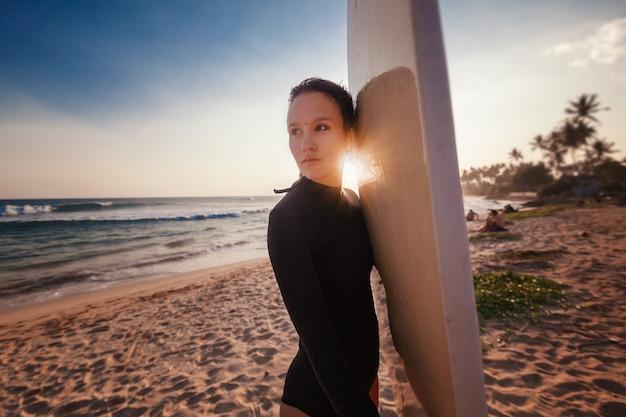 Hermosa mujer joven con cabello oscuro con una tabla de surf en la puesta de sol en el océano