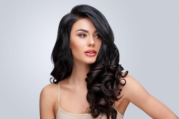 Hermosa mujer joven con un cabello rizado limpio y saludable