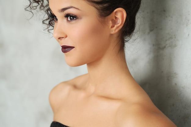 Hermosa mujer joven con cabello rizado negro y vestido negro brillante