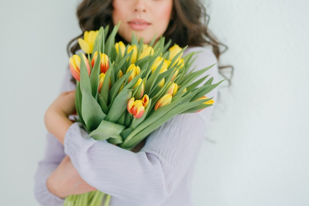Hermosa mujer joven con cabello rizado tiene un ramo de tulipanes.
