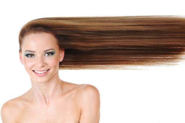 Hermosa mujer joven con cabello rubio largo sano en línea cerca de la cara