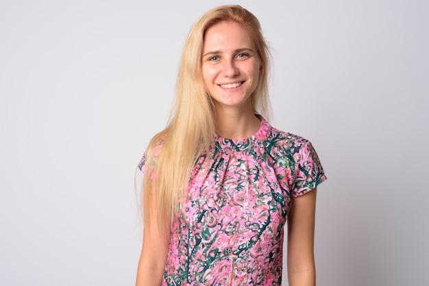 Hermosa mujer joven con cabello rubio vistiendo un vestido floral