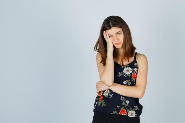 Hermosa mujer joven con la cabeza inclinada en la mano en blusa y mirando frustrado