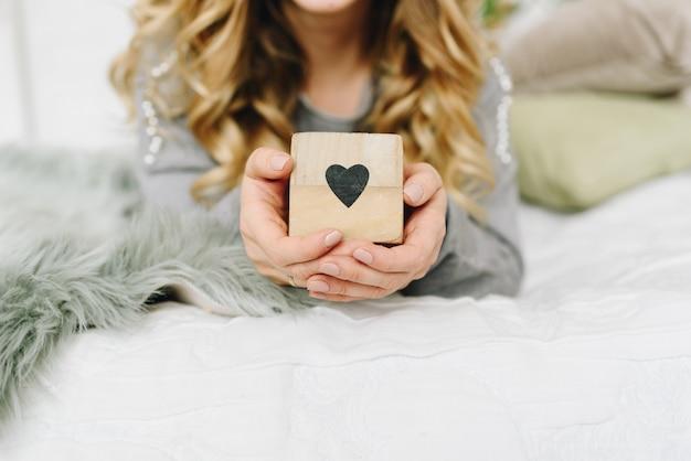 Hermosa mujer joven con caja con corazón negro