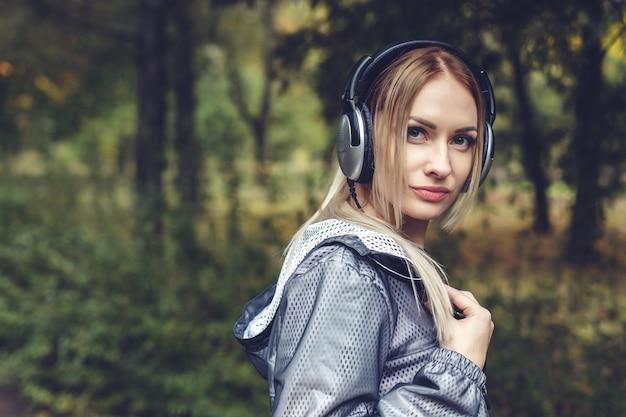 Hermosa mujer joven caminando por el parque de la ciudad, disfruta escuchando música con auriculares.