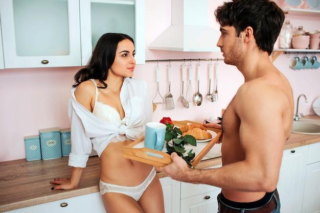 Hermosa mujer joven en camisa blanca mira en el hombre. estan en la cocina. un chico bien formado sostiene la bandeja con desayuno y rosa roja. son felices.