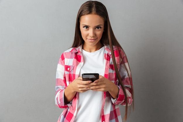 Hermosa mujer joven en camisa a cuadros, sosteniendo teléfonos