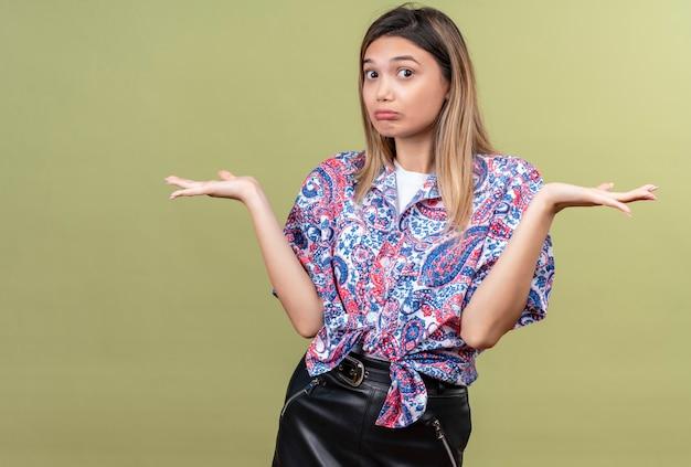 Una hermosa mujer joven con camisa estampada de paisley mostrando un gesto de impotencia y extendiendo sus manos mientras mira en una pared verde