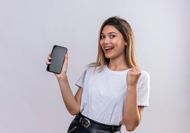 Una hermosa mujer joven en camiseta blanca sonriendo mientras muestra un espacio en blanco del teléfono móvil con el puño cerrado en una pared blanca