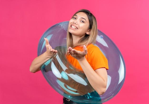 Una hermosa mujer joven con una camiseta naranja apuntando mientras está de pie sobre un anillo inflable en una pared rosa
