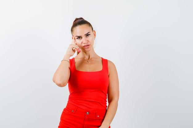 Hermosa mujer joven en camiseta roja, pantalones sosteniendo el dedo en las sienes y mirando pensativo, vista frontal.