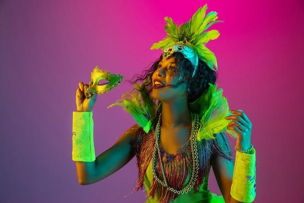 Hermosa mujer joven en carnaval, elegante disfraz de mascarada con plumas bailando en la pared degradada en neón