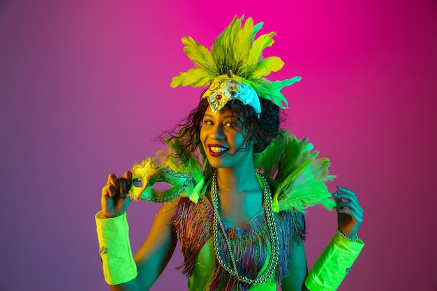 Hermosa mujer joven en carnaval, elegante disfraz de mascarada con plumas bailando sobre fondo degradado en neón.
