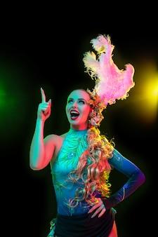 Hermosa mujer joven en carnaval, elegante disfraz de mascarada con plumas en pared negra en luz de neón