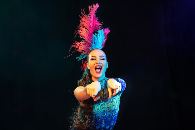 Hermosa mujer joven en carnaval, elegante disfraz de mascarada con plumas en pared negra en neón