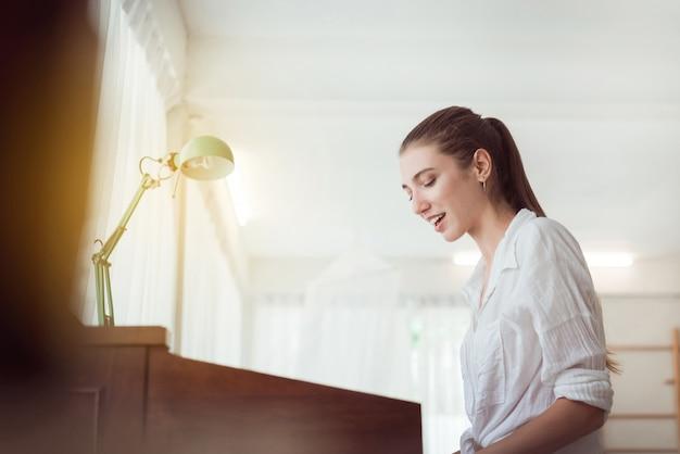 Hermosa mujer joven caucásica tocando piano eléctrico, feliz y sonriente, tiempo relajante