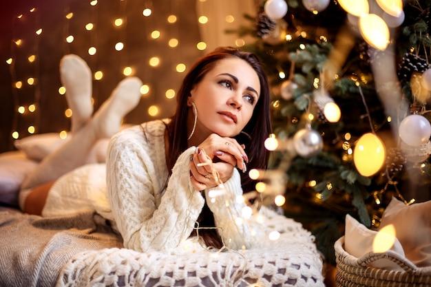 Hermosa mujer joven cerca de árbol de navidad, ambiente festivo, año nuevo y navidad.