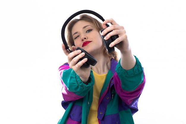 Hermosa mujer joven en chaqueta colorida y con auriculares