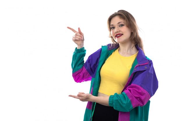 Hermosa mujer joven en chaqueta colorida señalando