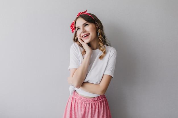 Hermosa mujer joven con cinta roja posando de ensueño. señora despreocupada con linda sonrisa de pie.