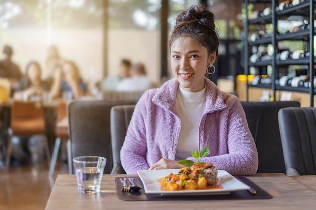 Hermosa mujer joven con comida en el restaurante