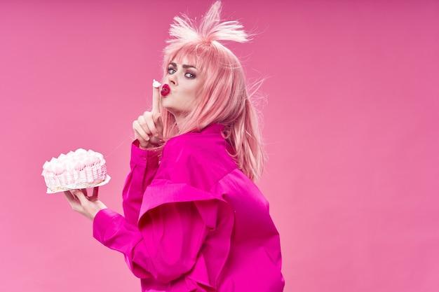 Hermosa mujer joven con comida en sus manos, una mujer comiendo en el estudio, superficie de color, sin dietas