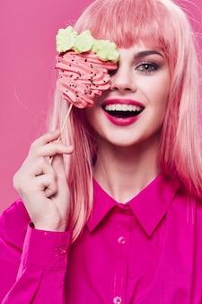 Hermosa mujer joven con comida en sus manos, una mujer comiendo en el estudio