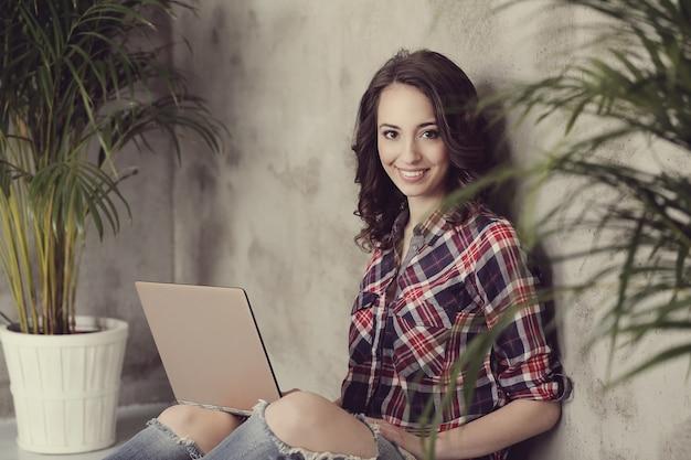 Hermosa mujer joven con computadora portátil