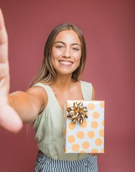 Hermosa mujer joven con caja de regalo floral con arco dorado tomando selfie