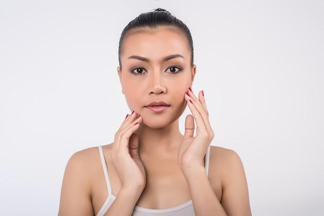 Hermosa mujer joven con la piel limpia y fresca toque propia cara