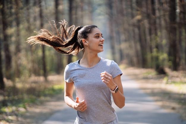 Hermosa mujer joven corriendo en el parque verde en un día soleado de verano
