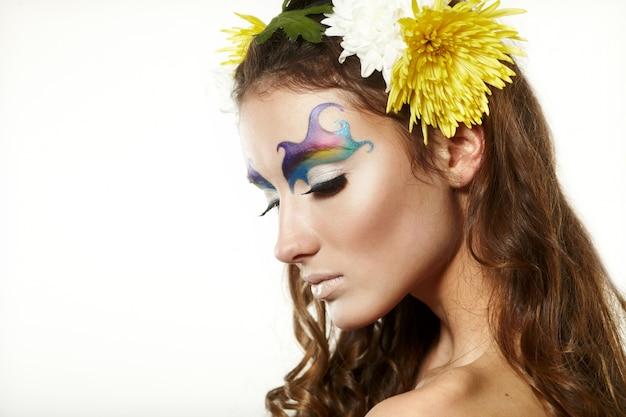 Hermosa mujer joven con delicadas flores en el pelo
