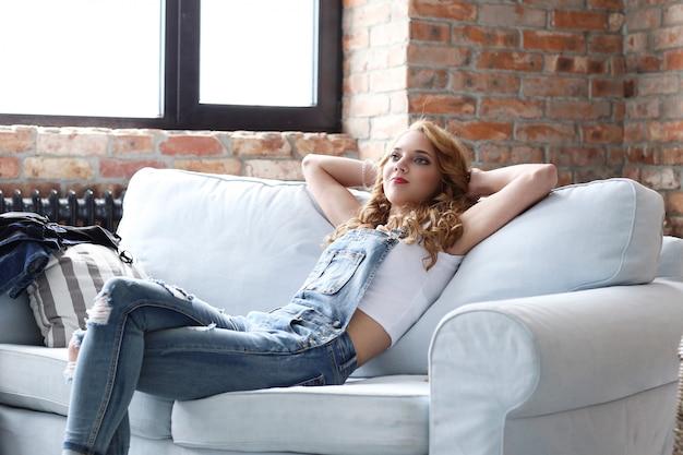 Hermosa mujer joven descansando en el sofá, sala de estar interior