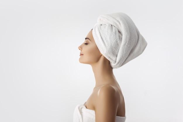 Hermosa mujer joven después del baño sobre fondo blanco